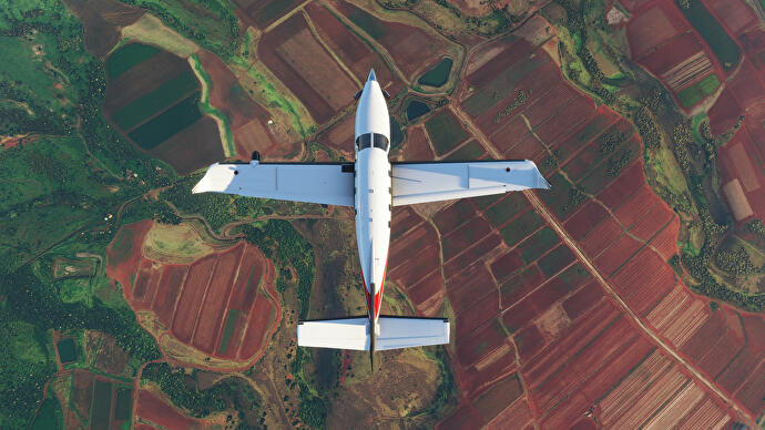 A top-down shot of a plane gliding over rusty red and green fields