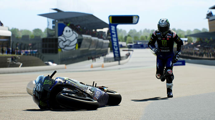 A rider runs back to his bike after a crash in MotoGP 21